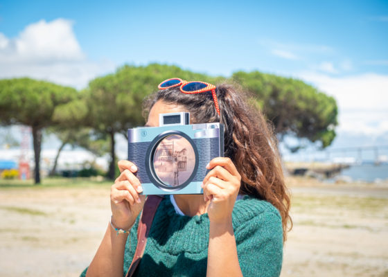 Jeune femme dont le visage est caché par un faux appareil photographique au bord de l'estuaire à Saint-Nazaire.
