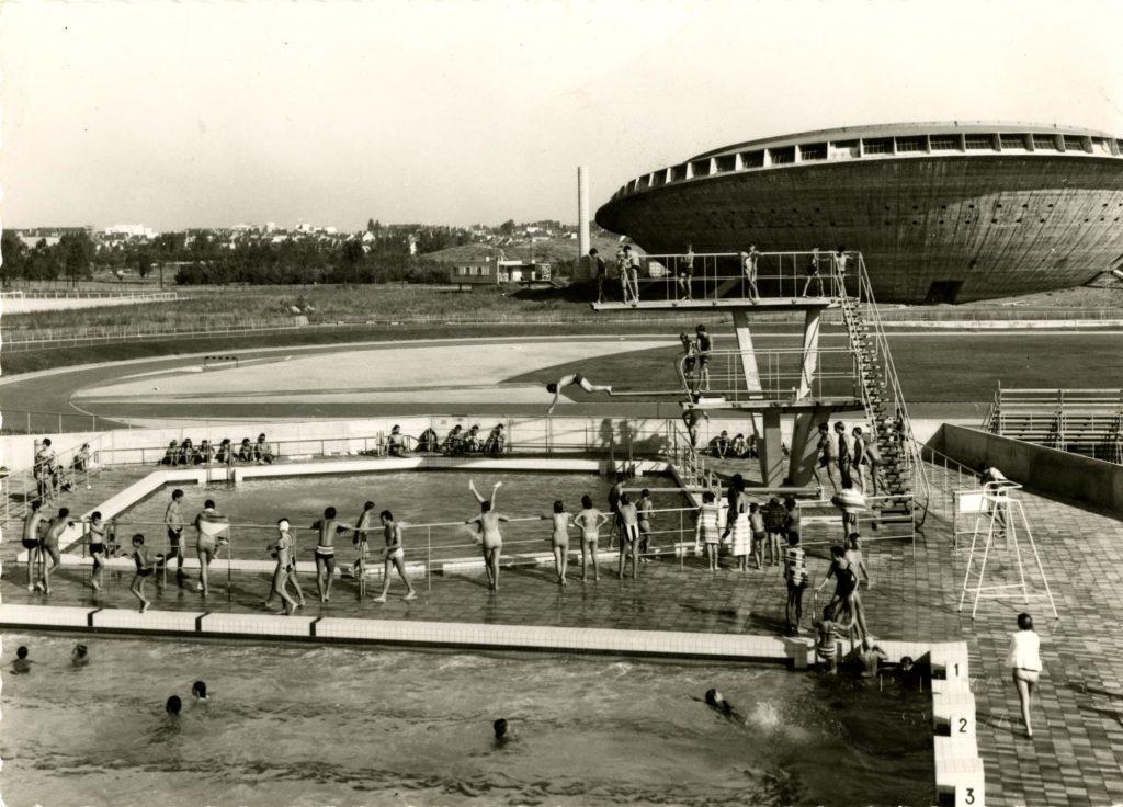 Photographie noir et blanc représentant une vue aérienne de deux bassins extérieurs de la piscine Léo Lagrange avec de nombreux baigneurs devant la Soucoupe.