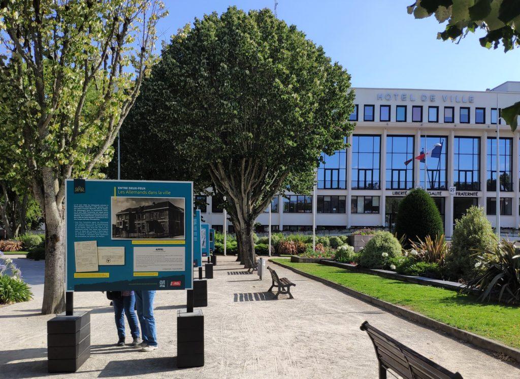 Panneau de l'exposition sur la Seconde Guerre mondiale avec derrière la façade de l'hôtel de ville de Saint-Nazaire