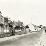 Carte postale noir et blanc représentant une rue en pente de Saint-Nazaire où circulent deux voitures dans les années 1930.