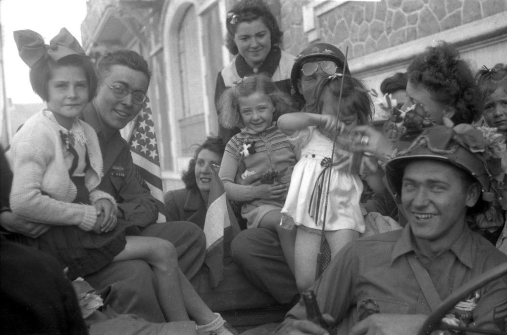 Photographie en noir et blanc représentant des soldats américains posant sur une jeep avec des enfants et des jeunes femmes à la Libération.