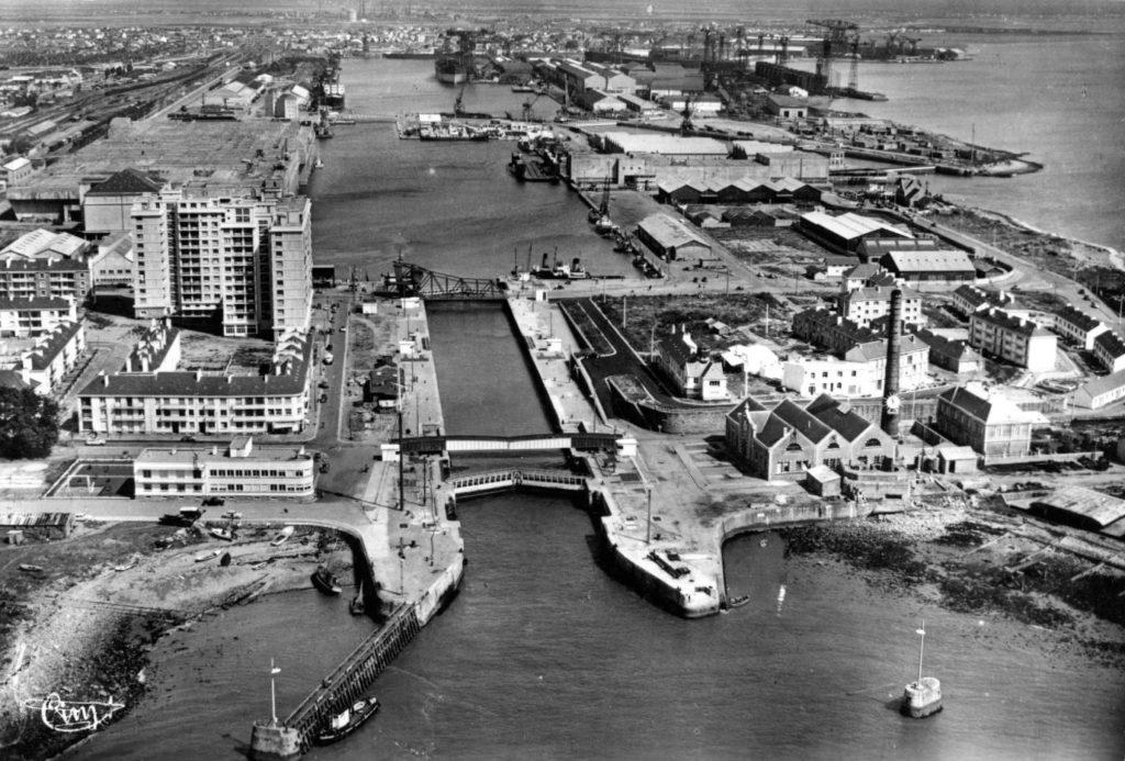 Photographie noir et blanc aérienne de l'avant-port de Saint-Nazaire avec l'usine élévatoire et des blockhaus.