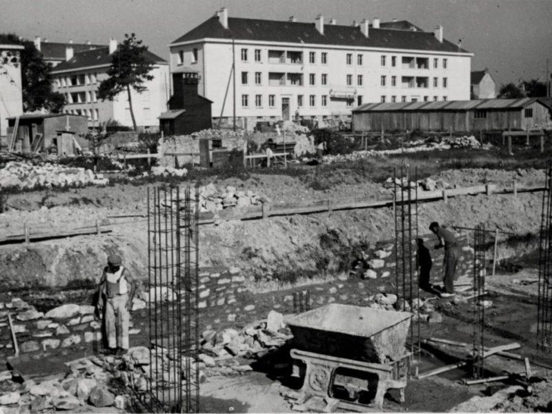Photographie noir et blanc représentant des hommes construisant une maison devant les HLM du quartier Gambetta à Saint-Nazaire évoqué dans une visite des Journées du Patrimoine.
