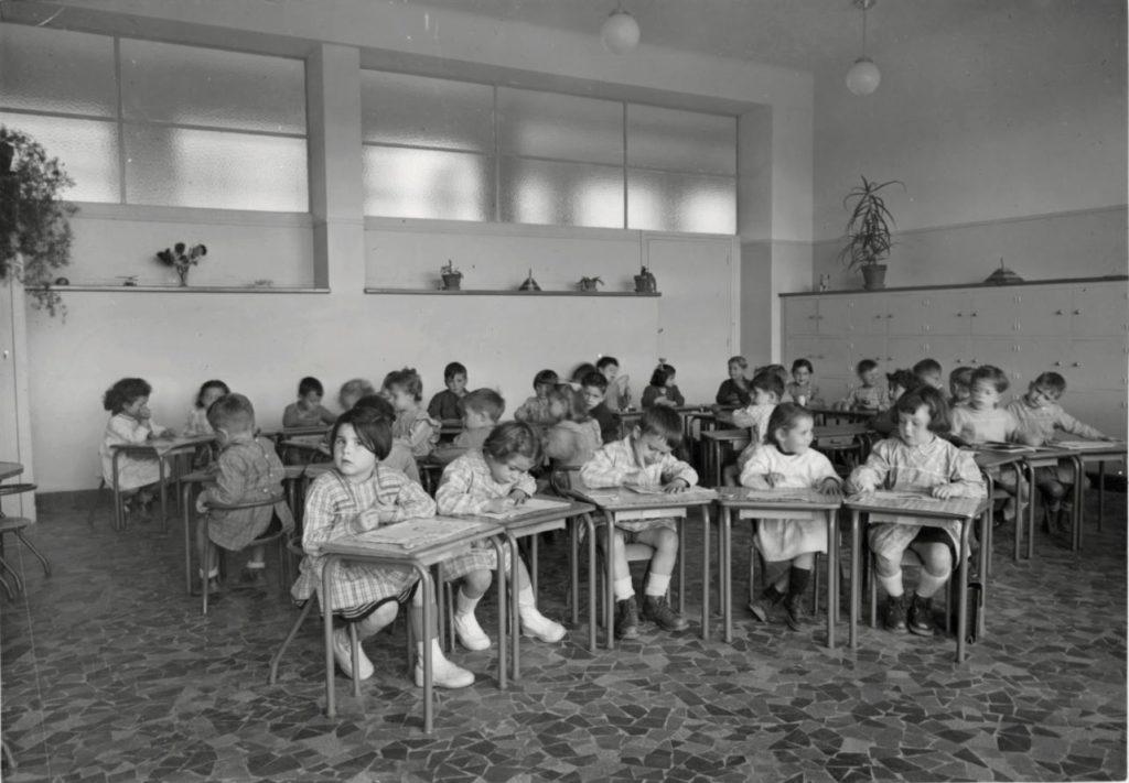 Photographie noir et blanc de maternels attablés dans leur salle de classe pour illustrer la visite de l'école moderne pour les Journées du Patrimoine.
