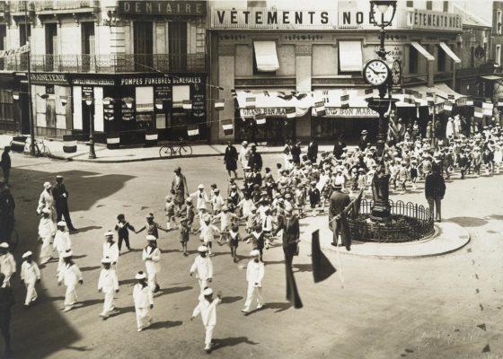 Photographie noir et blanc d'un défilé d'enfants déguisés en matelots sur la place Carnot pavoisée.