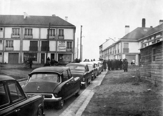 Photographie noir et blanc d'une file de voitures garées le long d'une rue dans le quartier du Petit Maroc, au fond un groupe d'hommes et un café.