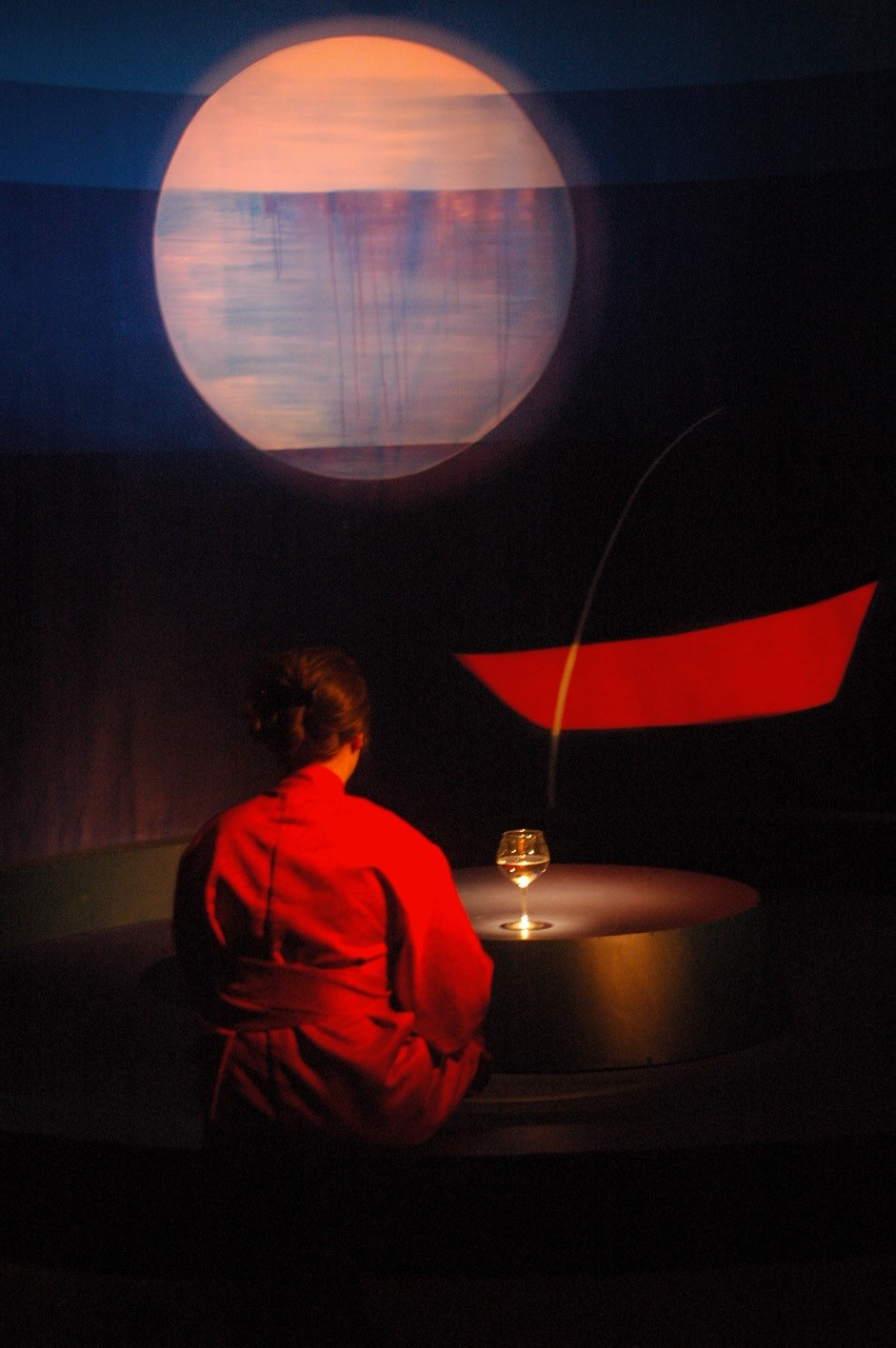 Photographie d'un spectacle musical représentant une jeune femme vêtue de rouge et assise en tailleur dos au spectateur dans une ambiance sombre.
