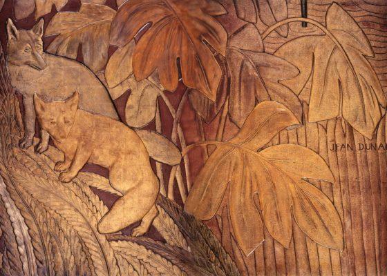 Détail d'une laque dorée représentant deux renards dans une végétation.