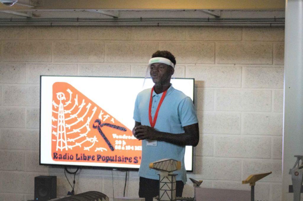 """Jeune homme debout avec une visière devant un écran projetant un autocollant de la Radio Libre Populaire lors de """"Ma solidarité"""" aux Journée du patrimoine."""