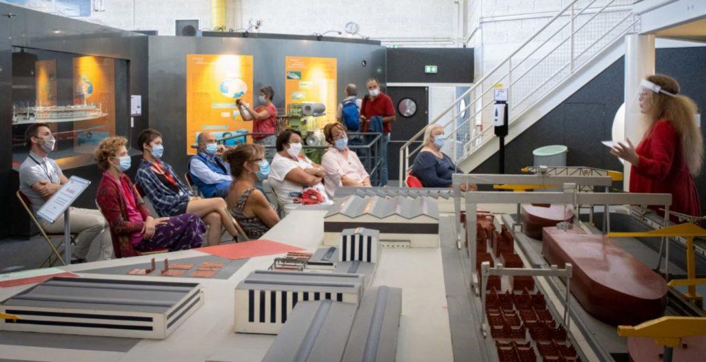 """Au premier plan, maquette des chantiers navals, derrière, une dizaine de personnes sont assises et écoute une médiatrice pendant """"Ma solidarité"""" aux Journées du patrimoine."""