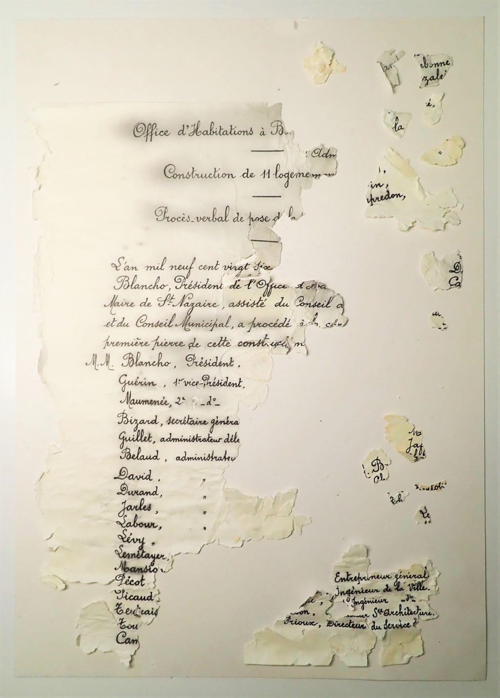 Photographie d'une feuille de papier morcelée sur laquelle est écrit un texte à la plume et à l'encre noire.