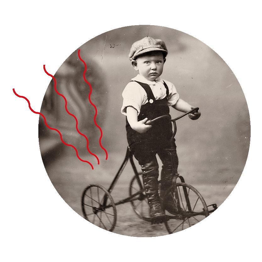 Photographie noir et blanc prise en studio d'un bébé sur un tricycle.