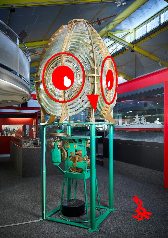 Photographie d'une lanterne de phare dans la salle de l'Écomusée sur laquelle ont été rajouté des yeux et un bec simulant une tête de chouette en référence à l'activité famille