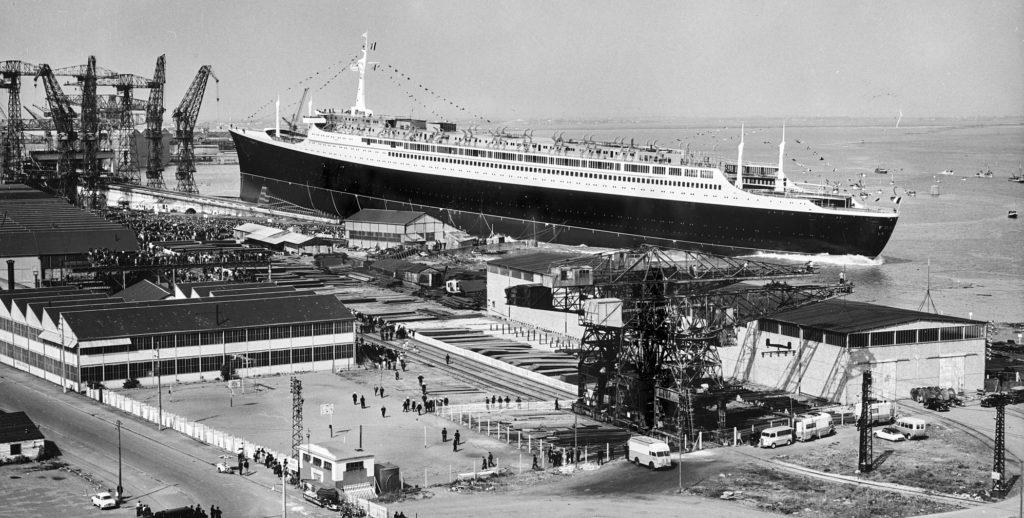 Vue des chantiers navals nazairiens au premier plan, derrière le paquebot France sans ses cheminées est en train de glisser dans l'eau lors de son lancement