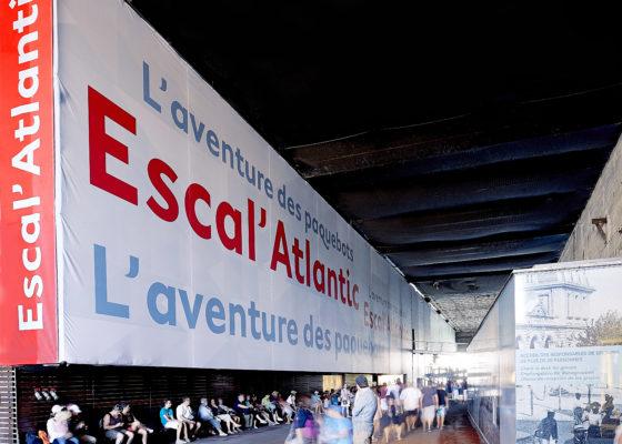 Entrée d'Escal'Atlantic dans la base sous-marine avec une bâche recouvrant le mur et présentant le musée. Devant de nombreux visiteurs.