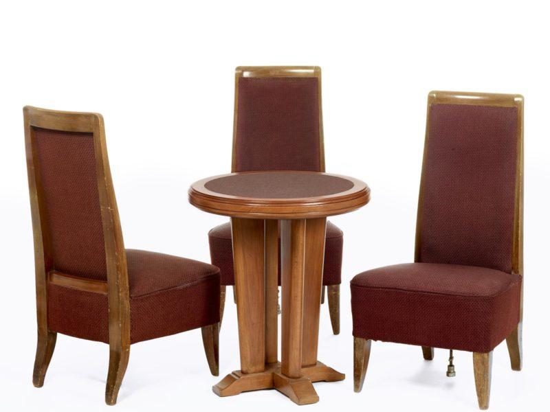 Trois chaises et une table de jeu ronde en bois et tissu bordeaux.
