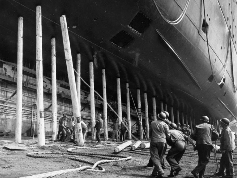 Photographie en noir et blanc d'un groupe d'ouvriers tirant sur une corde pour faire tomber un pieu de bois sur lequel repose le paquebot France.