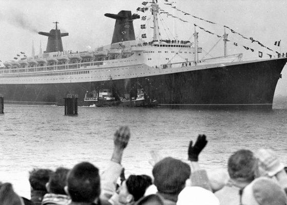Paquebot France sortant du port de Saint-Nazaire, au premier plan une foule agite les bras.