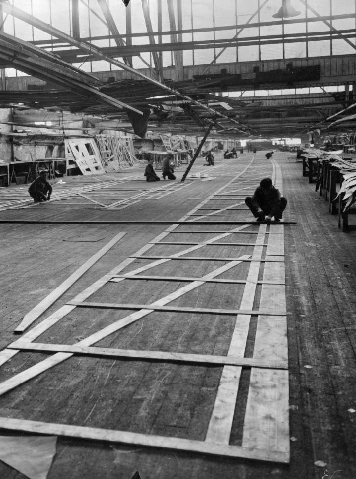 Photographie noir et blanc de la salle à tracer des chantiers navals nazairiens avec des ouvriers accroupis en train de tracer des formes au sol.