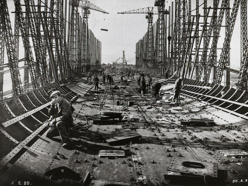 Photographie noir et blanc d'ouvriers travaillant au rivetage de la coque du paquebot Normandie en 1931.