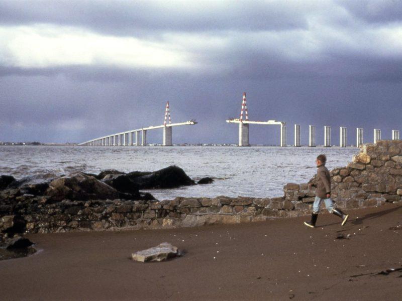 Photographie d'un enfant courant sur une plage devant un muret, derrière l'estuaire de la Loire et le pont de Saint-Nazaire en cours de construction.
