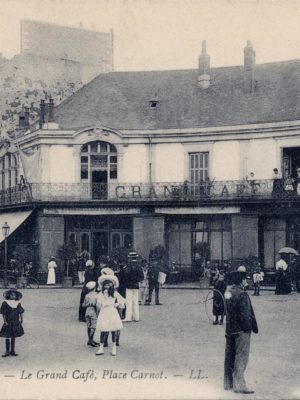 Carte postale avec une photo en noir et blanc représentant une foule devant le Grand Café, place Carnot à Saint-Nazaire.