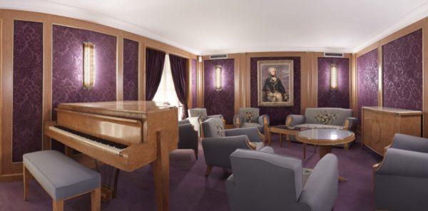 Photographie couleur du salon de musique du paquebot Liberté, avec ses murs violets, ses meubles et son piano conçus par Baptistin Spade.