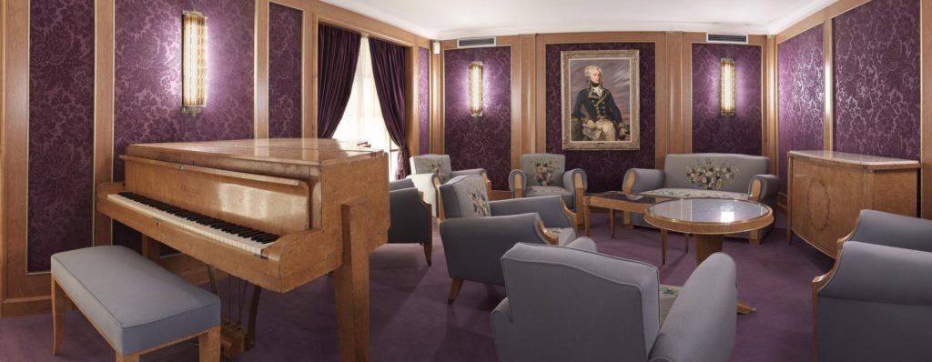 Reconstitution du salon de musique du paquebot Liberté à Escal'Atlantic avec ses meubles et son piano et une tapisserie violette.