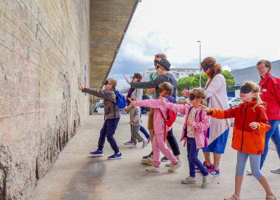 Enfants et adultes avec un bandeau sur les yeux s'avançant vers un mur en béton de la base.
