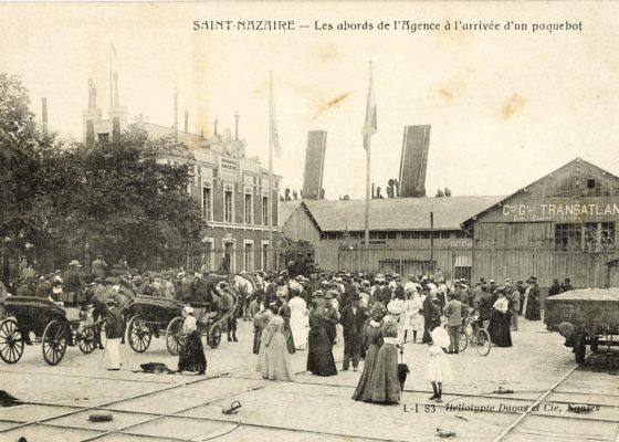 Foule devant les grilles de l'agence de la Compagnie Générale Transatlantique à Saint-Nazaire vers 1900.