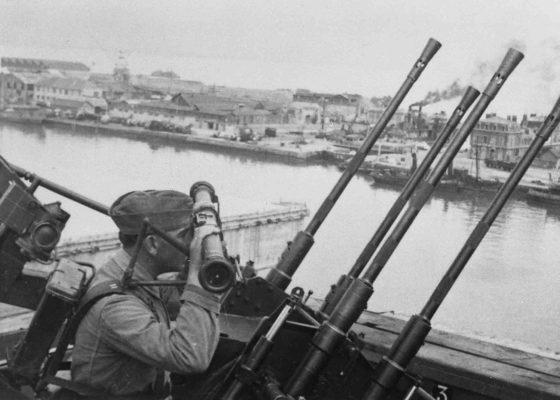 Photographie en noir et blanc illustrant un soldat allemand qui surveille le port depuis le toit du terminal frigorifique.