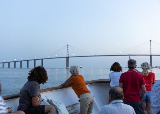 Passagers appuyés sur le pont du bateau de croisière et regardant le pont de Saint-Nazaire à la nuit tombée.