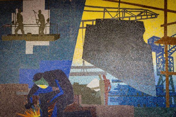 Photographie d'une mosaïque colorée représentant les chantiers navals et un soudeur au premier plan dans des tons colorés.