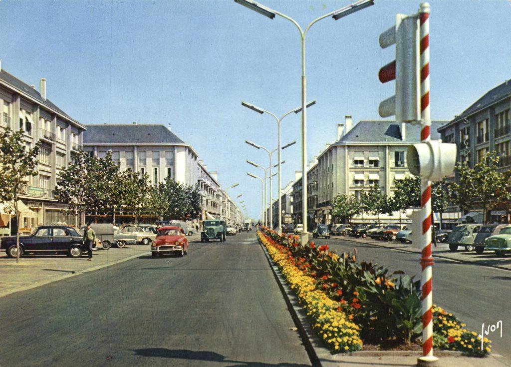 Voitures et camion roulant sur l'avenue de la République pavoisée dans les années 1950.