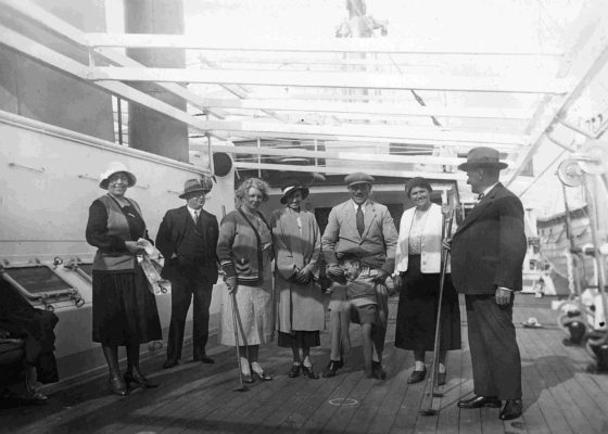Photographie en noir et blanc illustrant des passagers sur le pont d'un paquebot avec un jeu de shuffle board.