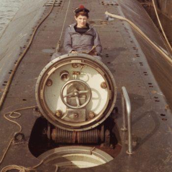 Sous-marinier en uniforme posant devant l'écoutille du sous-marin Espadon.