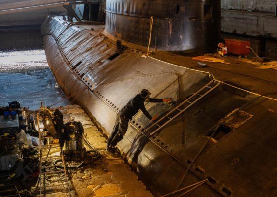Ouvrier debout sur un ponton flottant en train de meuler la coque externe du sous-marin Espadon.