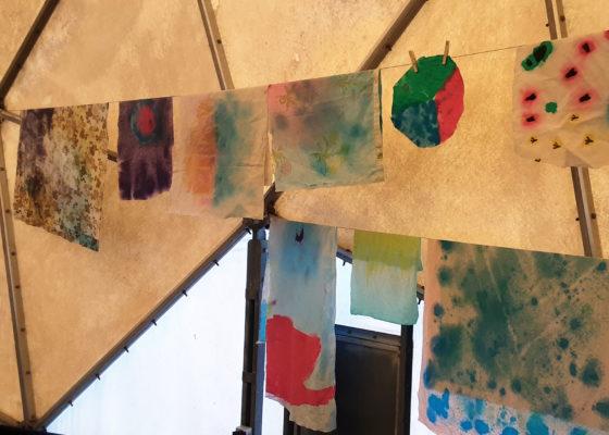 Photographie d'une exposition de dessins réalisés par des enfants accrochés sur des cordes à linge dans le radôme.
