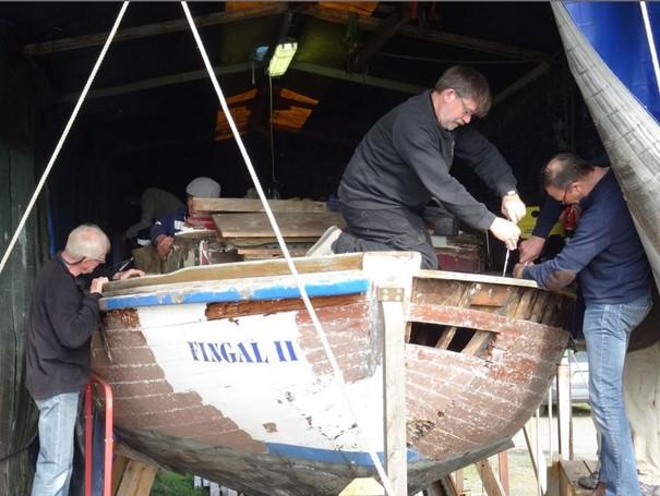 Quatre hommes s'affairent à la restauration d'un ancien navire.
