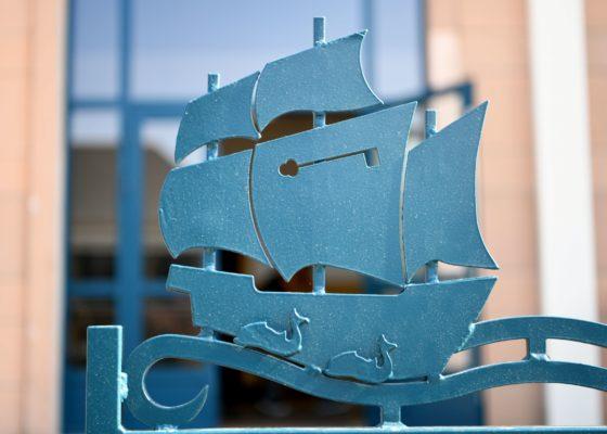 Photographie d'un détail de la grille d'entrée des bains douches de Saint-Nazaire, représentant un voilier avec une clé.