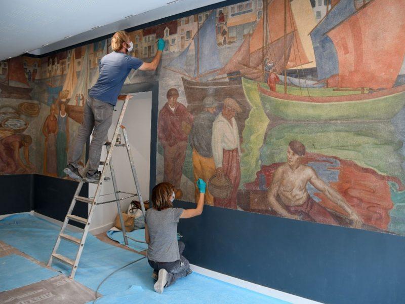 Deux restaurateurs font des retouches sur la fresque de l'ancienne école Jean Jaurès.
